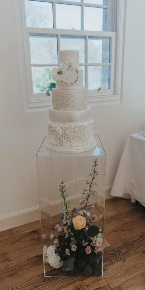 white wedding cake on floral stand
